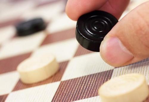 Черная шашка и доска